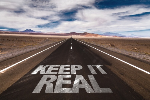 Keep it Real written on desert road